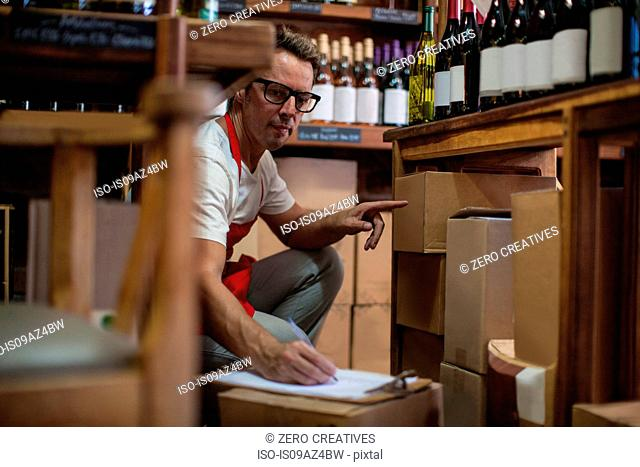 Man in wine shop stock taking bottles of wine