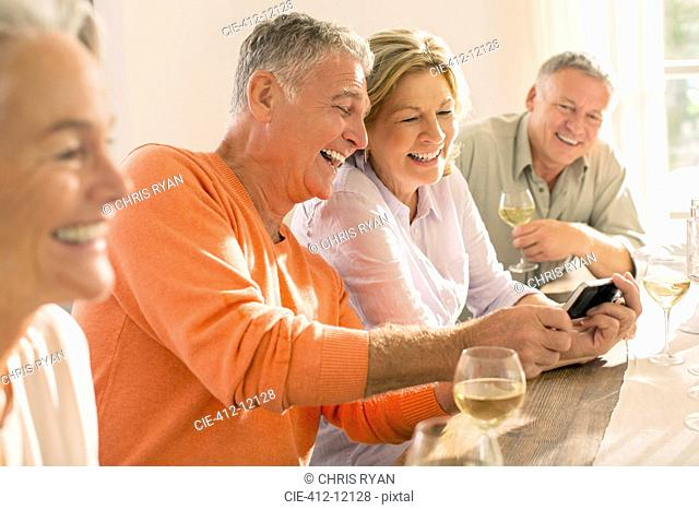 Senior couples drinking wine and looking at cell phone