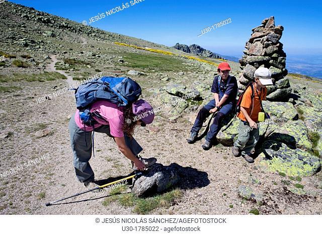 Mountaineers resting next to a boundary stone, in Biosphere Reserve of Sierra de Béjar and Francia  Salamanca  Candelario  Castilla y León  Spain