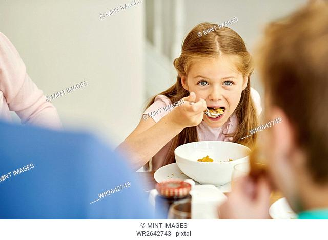 A family eating breakfast. A girl eating cereal with a spoon