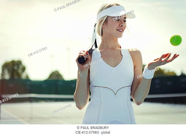Smiling young female tennis player holding tennis racket and tennis ball on tennis court