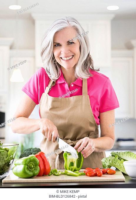 Portrait of smiling Caucasian woman slicing vegetables