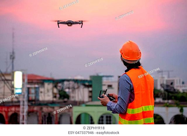 Young Asian engineer flying drone over construction site during sunset. Using unmanned aerial vehicle (UAV) for land and building site survey in civil...