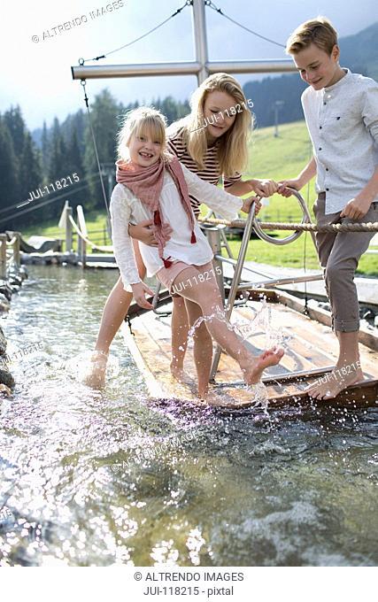 Children Playing On Wooden Raft In Adventure Park