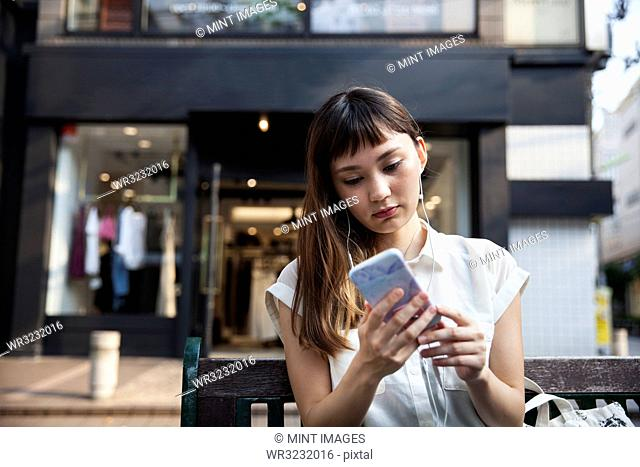 Japanese woman with long brown hair wearing white short-sleeved blouse standing in a street, looking at mobile phone