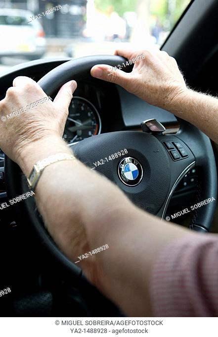 Mature Mans hands on steering wheel on BMW