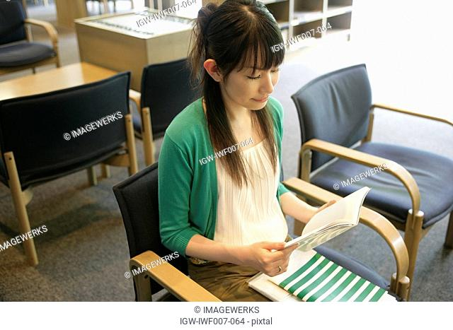 A young woman sits on the chair while she reads a book in the library