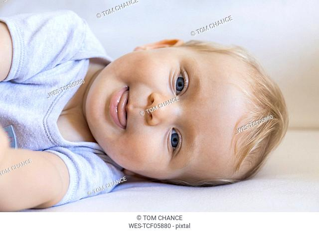 Portrait of blond baby girl lying on couch