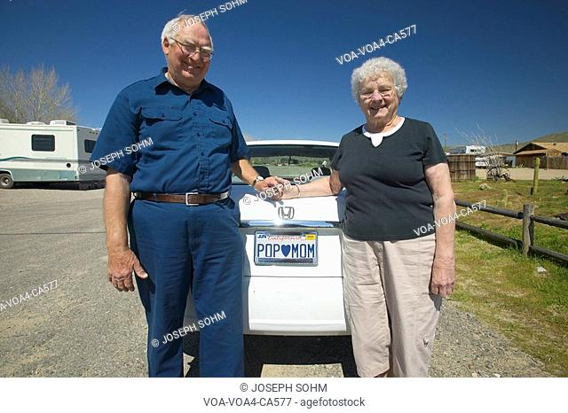 "Elderly couple pose with California license plate that reads ""Pop loves Mom"""
