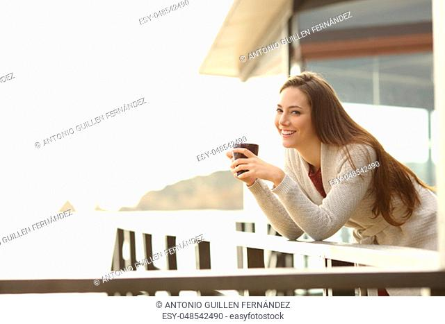 Happy hotel guest holding coffee looking at you