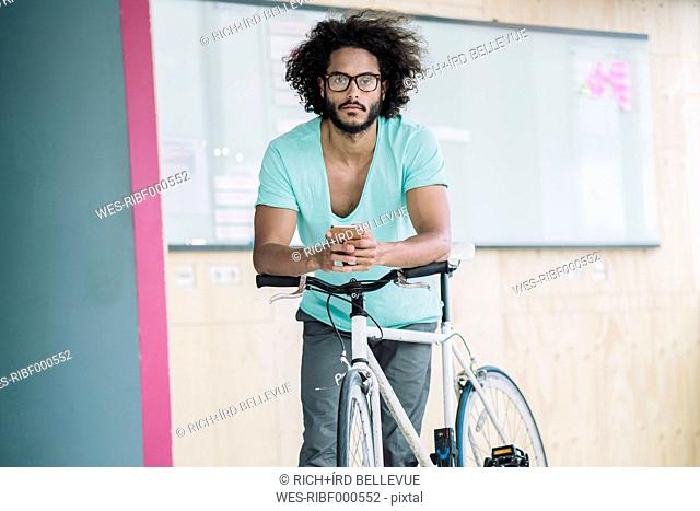 Young man leaning on bicycle, using smart phone