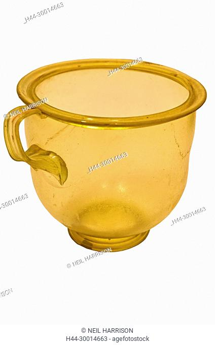 Ancient roman green glass cup from the 2nd century AD, with shaped handle. Isolated against a white background