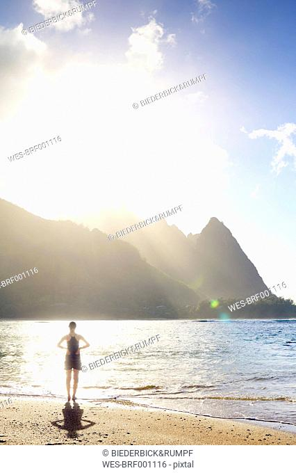 USA, Hawaii, Hanalei, woman standing on Haena Beach, View to Na Pali Coast in the evening light