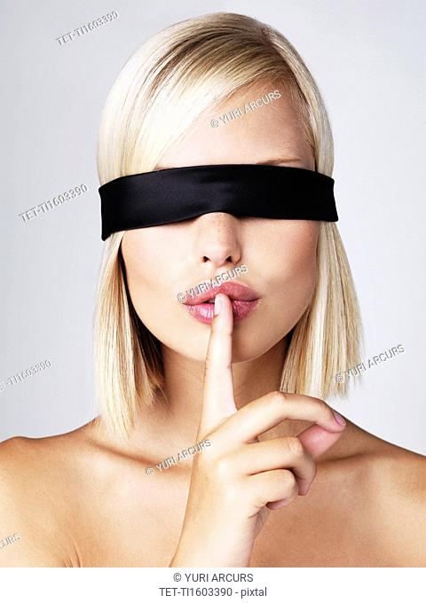Young woman wearing blindfold with finger on lips, studio shot