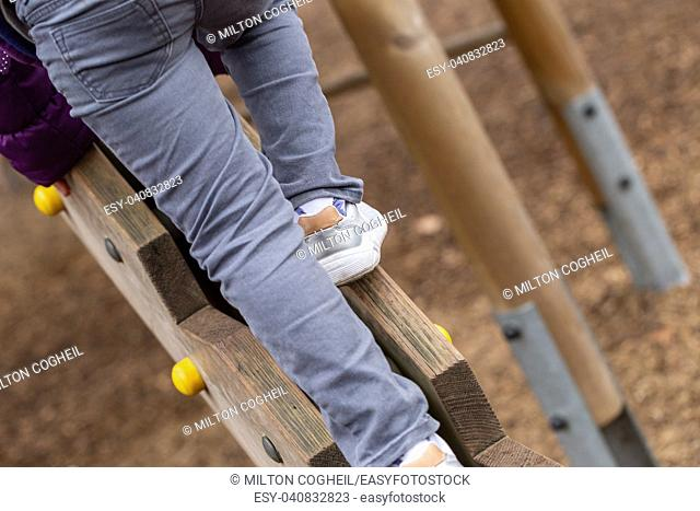 A young boy on a wooden climbing frame in Battersea Park, London