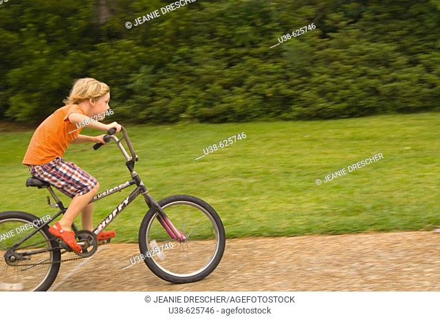 6 year old boy riding a bike very fast. Point Harbor, North Carolina. USA