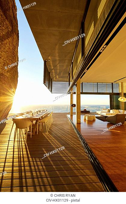 Dining table on modern luxury patio with sunset ocean view