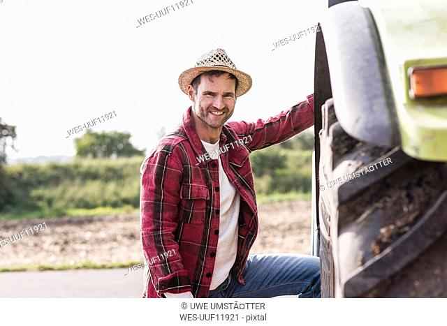 Portrait of confident farmer with tractor