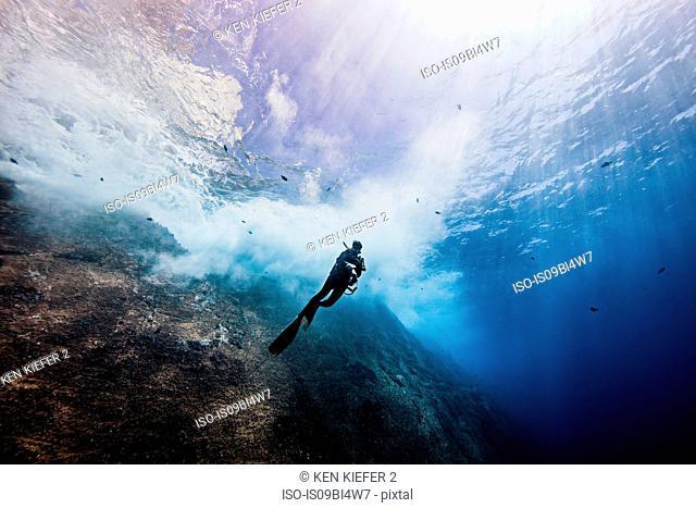 Underwater view of female diver exploring roca partida pinnacle, Socorro, Baja California, Mexico