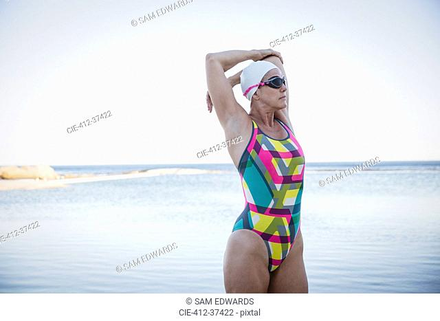 Female open water swimmer stretching arm at ocean