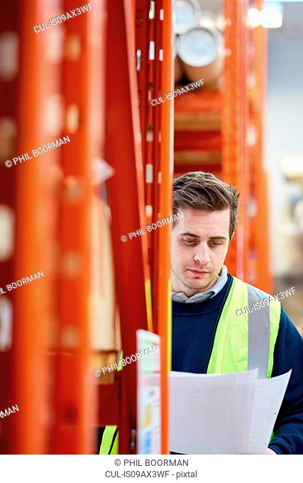 Male factory worker checking paperwork in factory warehouse
