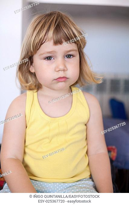 portrait of blonde two years old child with yellow shirt looking with sad face