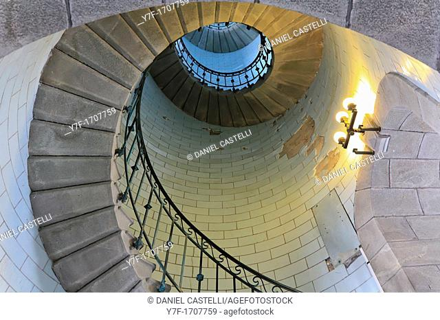 Angle shot of a lighthouse's spiral stair lighted by electric lamp, vortex