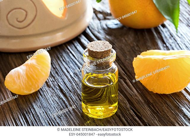 A bottle of tangerine essential oil on a wooden table, with tangerines and an aroma lamp in the background