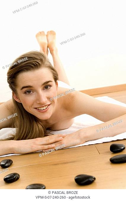 Portrait of a young woman getting lastone therapy and smiling