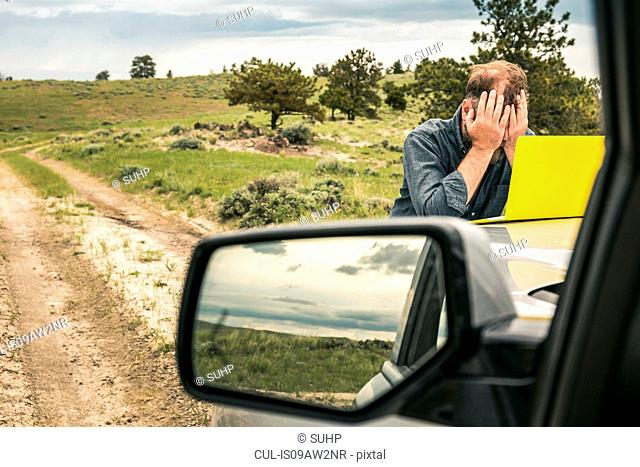 Man on dirt track road trip with head in hands at car bonnet, Cody, Wyoming, USA