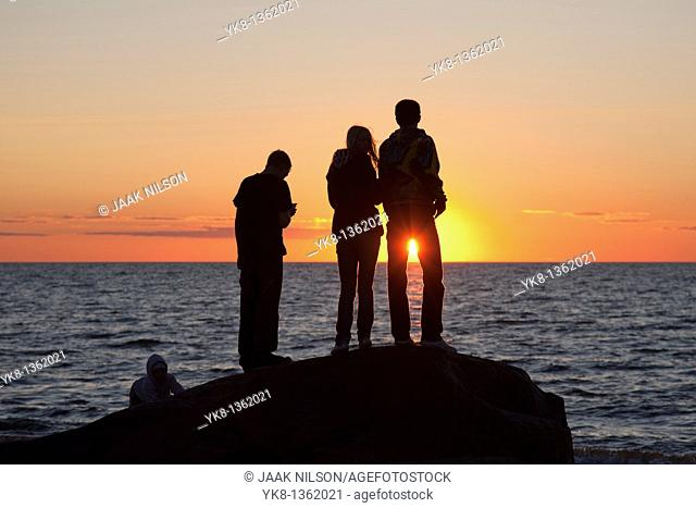 People Silhouettes at Sunset on Beach