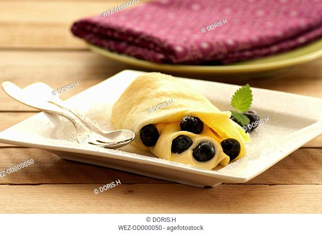 Crepe with custard and blueberries on plate, close up