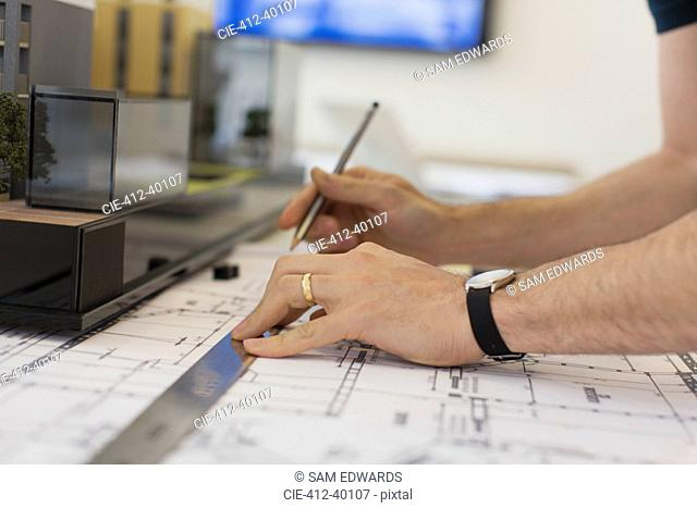 Close up architect drafting blueprint with ruler and pencil