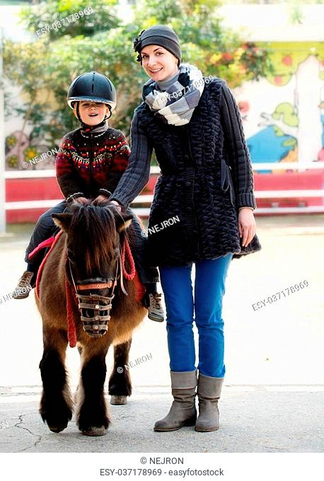 Mother riding her son on a pony wearing protective helmet