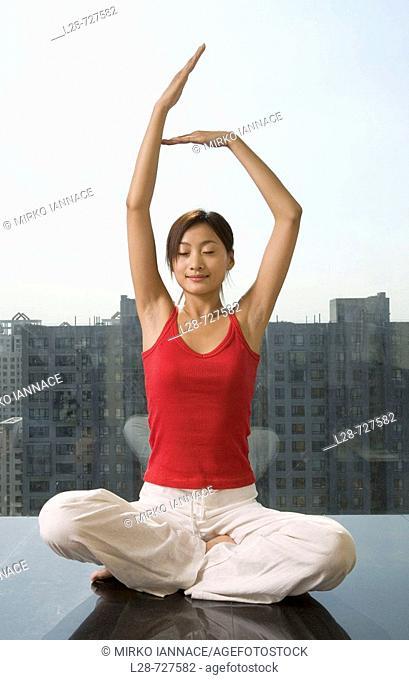 Woman sitting in yoga position on floor