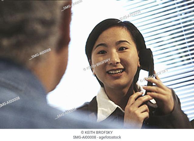Female executive holding telephone talking with Caucasian male executive