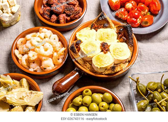 Tapas food, served in small bowls cold meat, goat cheese. A meal for sharing