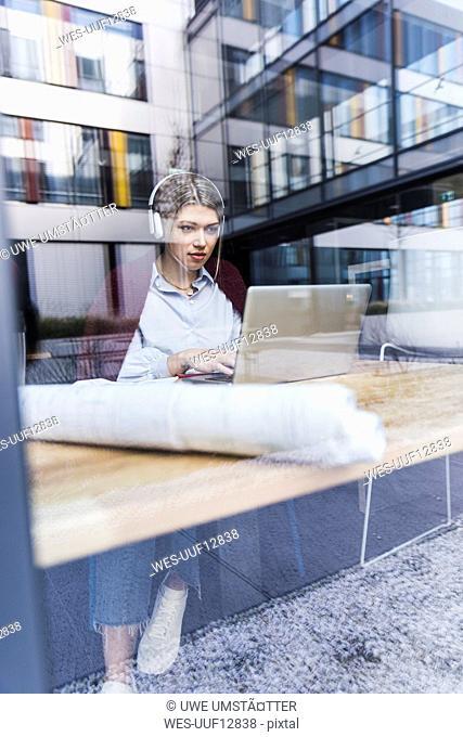 Young woman wearing headphones using laptop behind windowpane