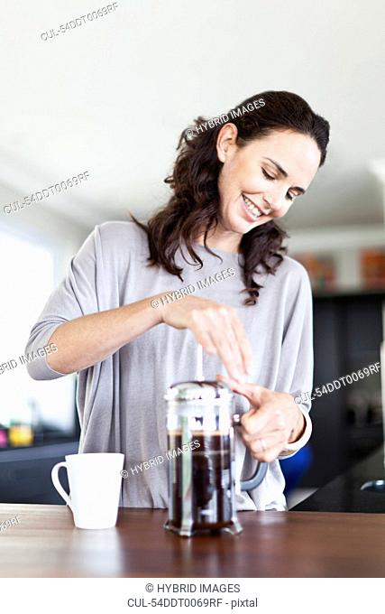 Woman making french press coffee