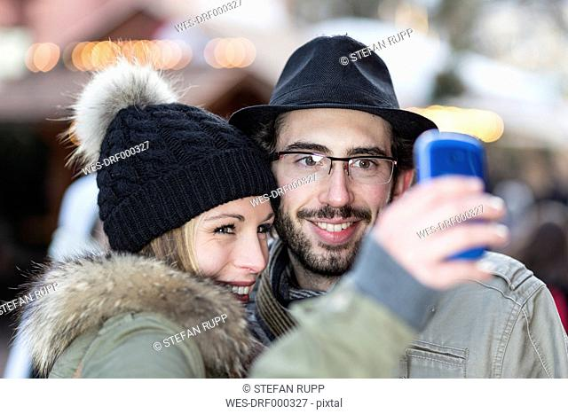 Portrait of smiling young couple photographing themself