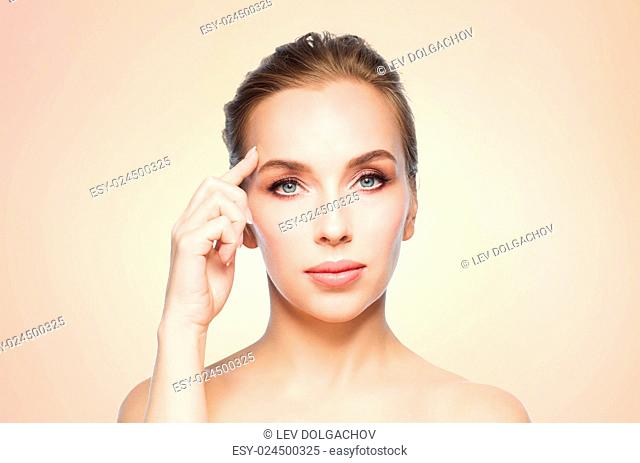 beauty, people and plastic surgery concept - beautiful young woman showing her forehead over beige background
