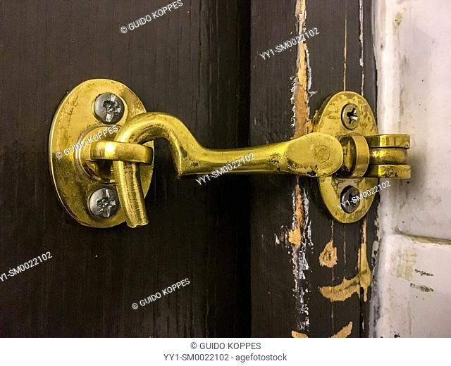 Paris, France. Simple doorhook, locking a toilet and bathroom door from the inside at a small cafe and restaurant