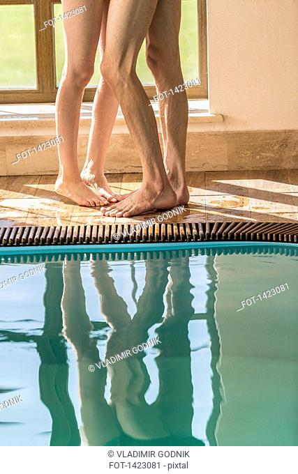 Low section of passionate couple standing at the edge of swimming pool