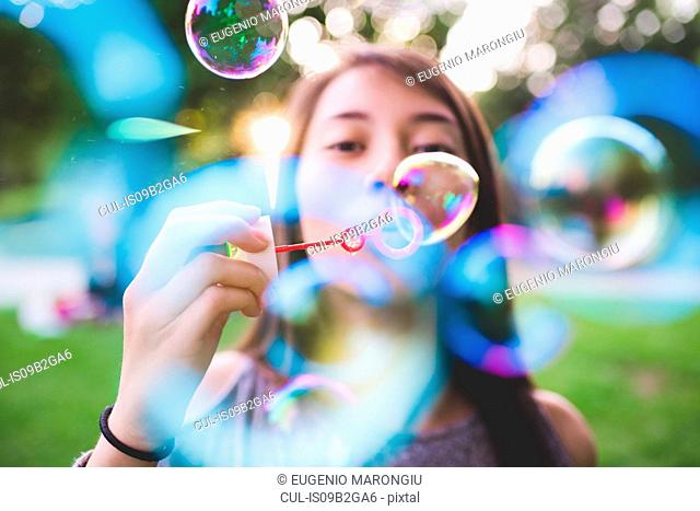 Close up of young woman in park blowing bubbles