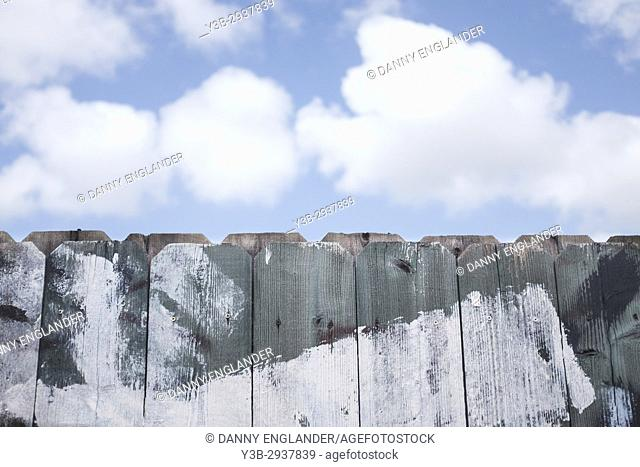 An old worn and weathered wooden fence with blue sky and clouds in the background