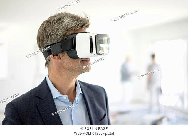 Man in suit wearing VR glasses in building under construction