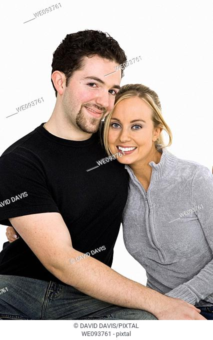 Studio photograph of young Caucasian couple posing with their arms around each other on a white background