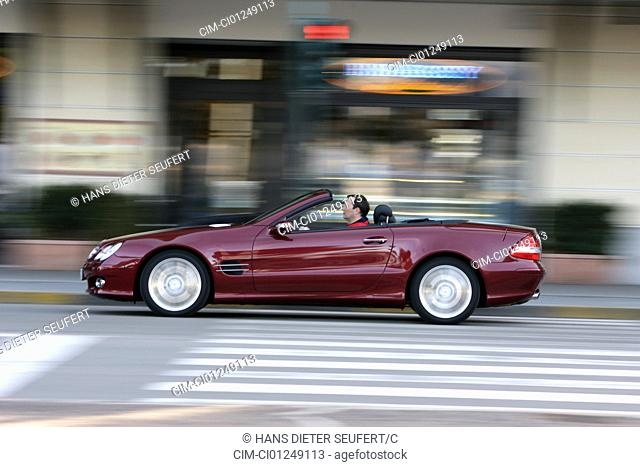 Mercedes SL 500, ruby colored, model year 2006-, driving, side view, City, open top