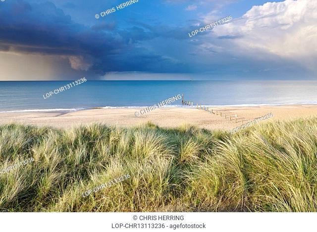 England, Norfolk, Horsey. Sand dunes at Horsey and a dramatic summer storm out at sea