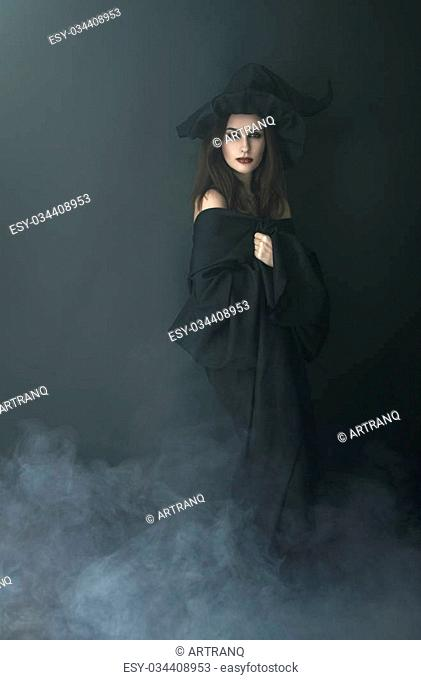 slender witch in a smoke on a black background